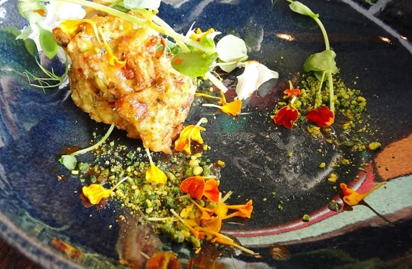 The Zucchini Fritters with edible flowers and crushed pistachios