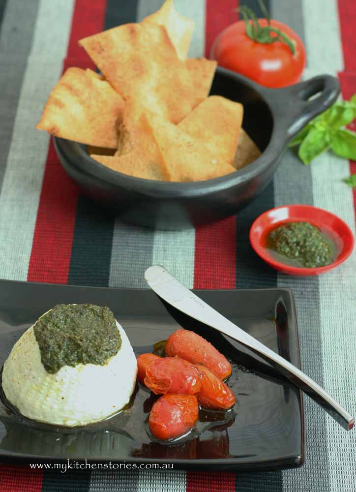 Ricotta baked and put on a black plate with tomatoes