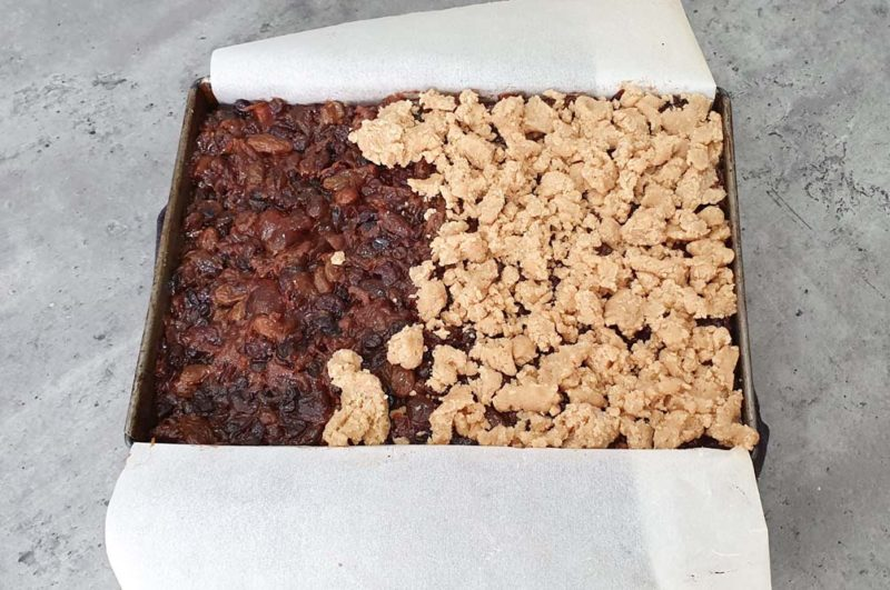 Topping a fruit mince slice with crumble
