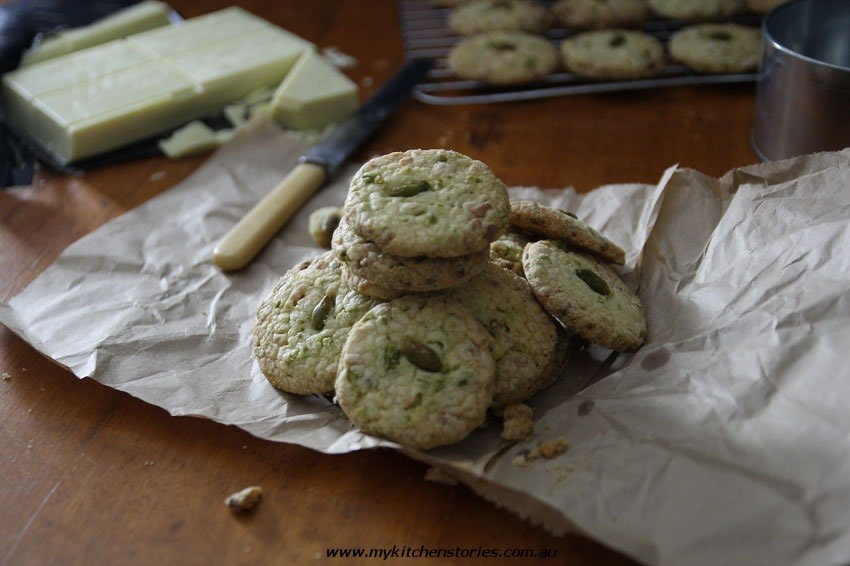 white chocolate chip pistachio cookies on a cake rack wirth pistachios