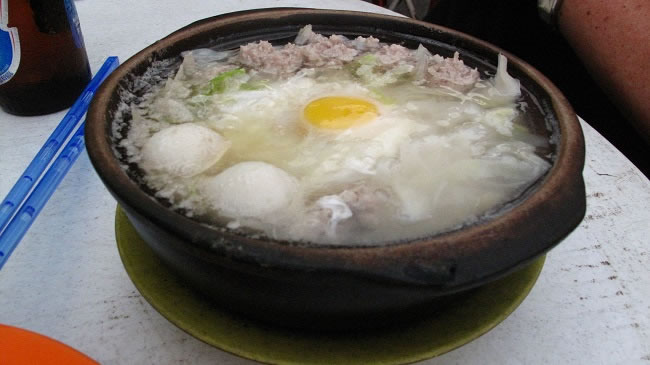 Local speciality rice noodle soup with pork and soft egg that breaks when you dig in