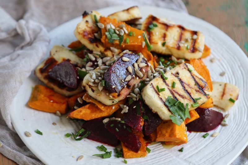 Beetroot, grilled haloumi and roasted pumpkin with dressing on a white plate