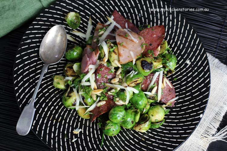 Brussels sprouts, crispy salami and smoked mozzaella salad on a black plate