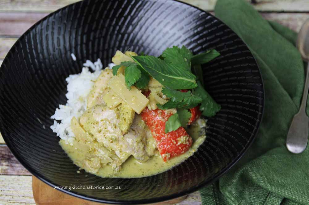 Green curry chicken in a black bowl with steamed rice.