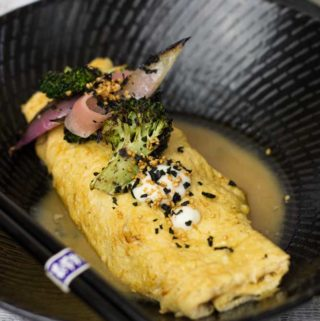 Miso Dashi Omelette on a black plate