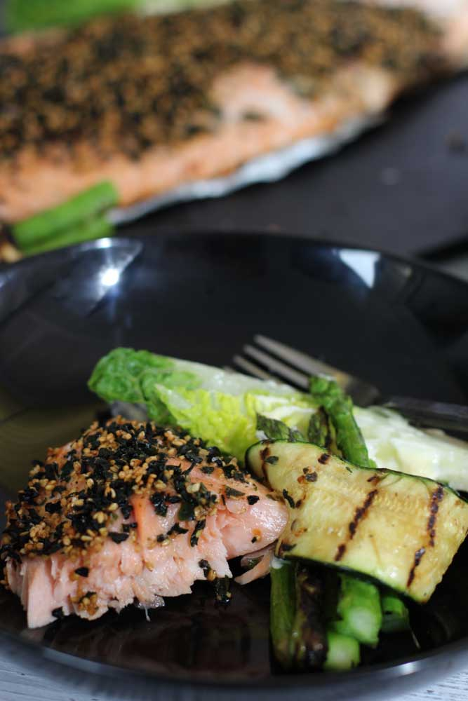 BBQ Salmon on a black plate with sesame and zucchini