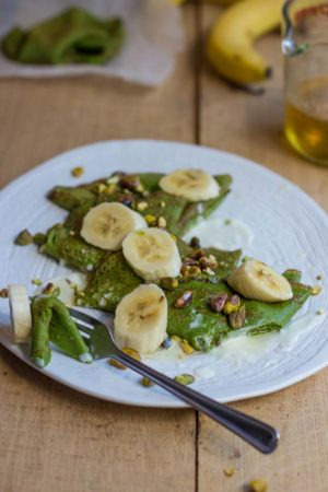 Green pancakes on a white plate with bananas
