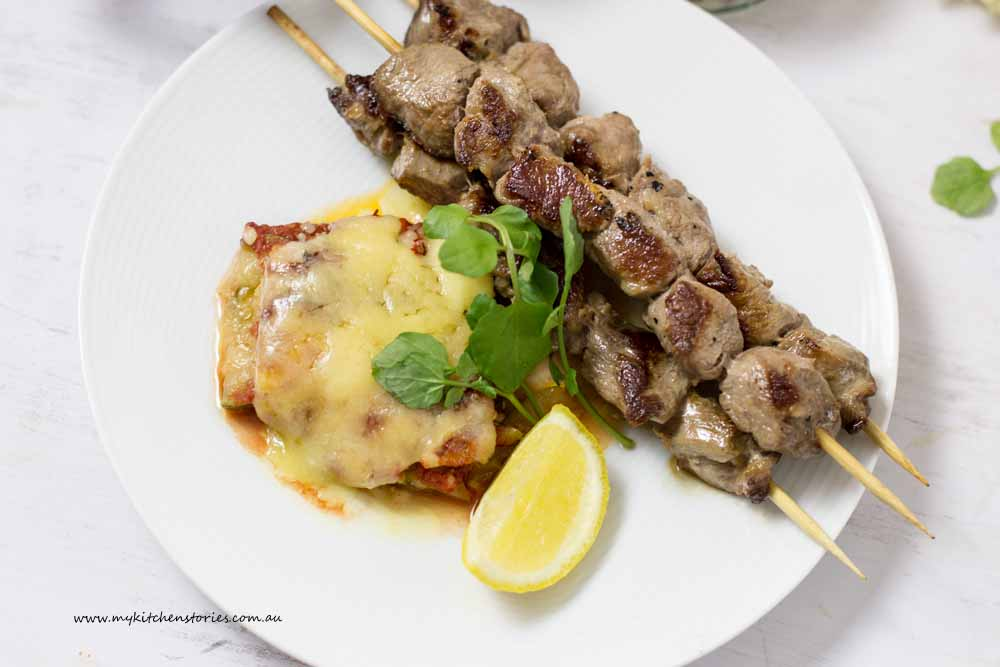 Lamb skewers Zucchini cheese bake on a white plate