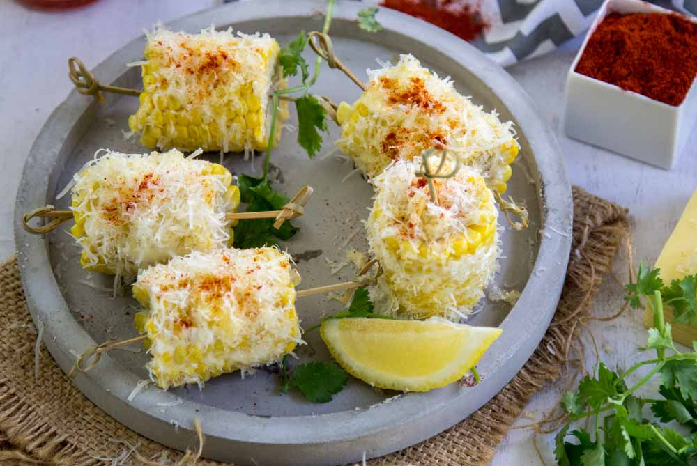 Cheesy Corn on the cob on a grey plate
