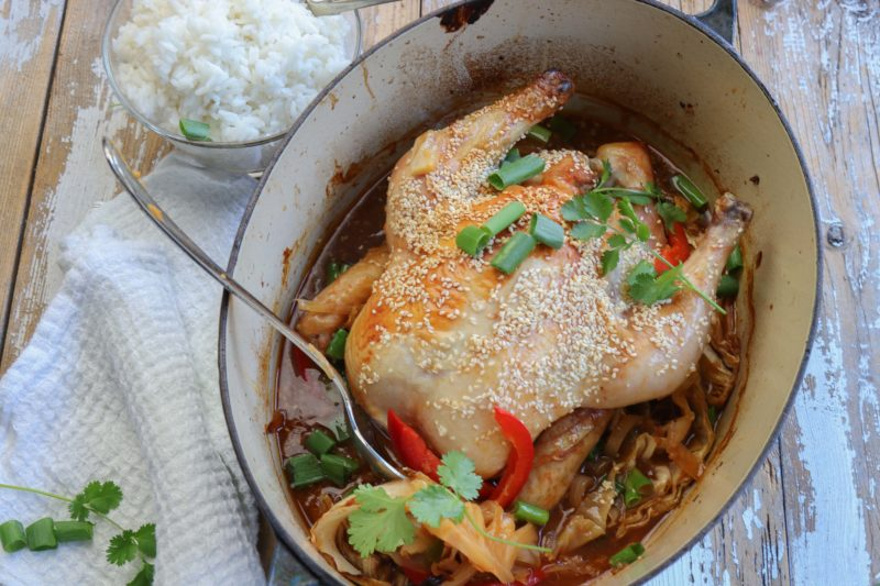 Golden roasted chicken with ginger and sesame in a blue pot