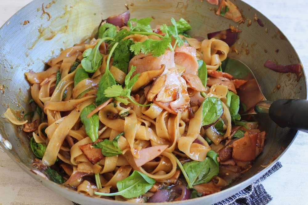 Ham stirfry with flat rice noodles in a wok
