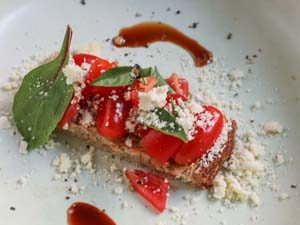 Tomatoes and basil on a white plate with olive oil powder