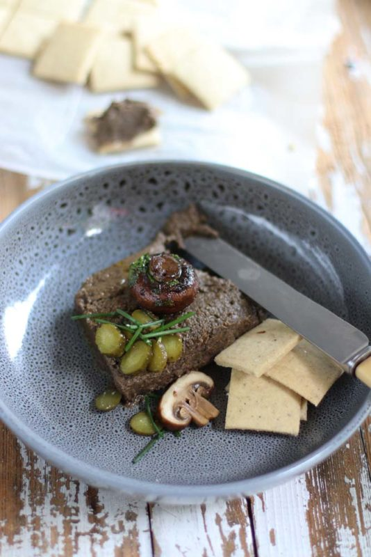 Mushroom Pate with gluten free crackers and a knife in a Gray bowl
