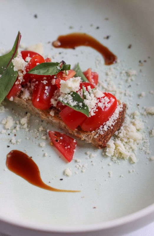 Tomatoes and basil on a plate with powdered olive oil