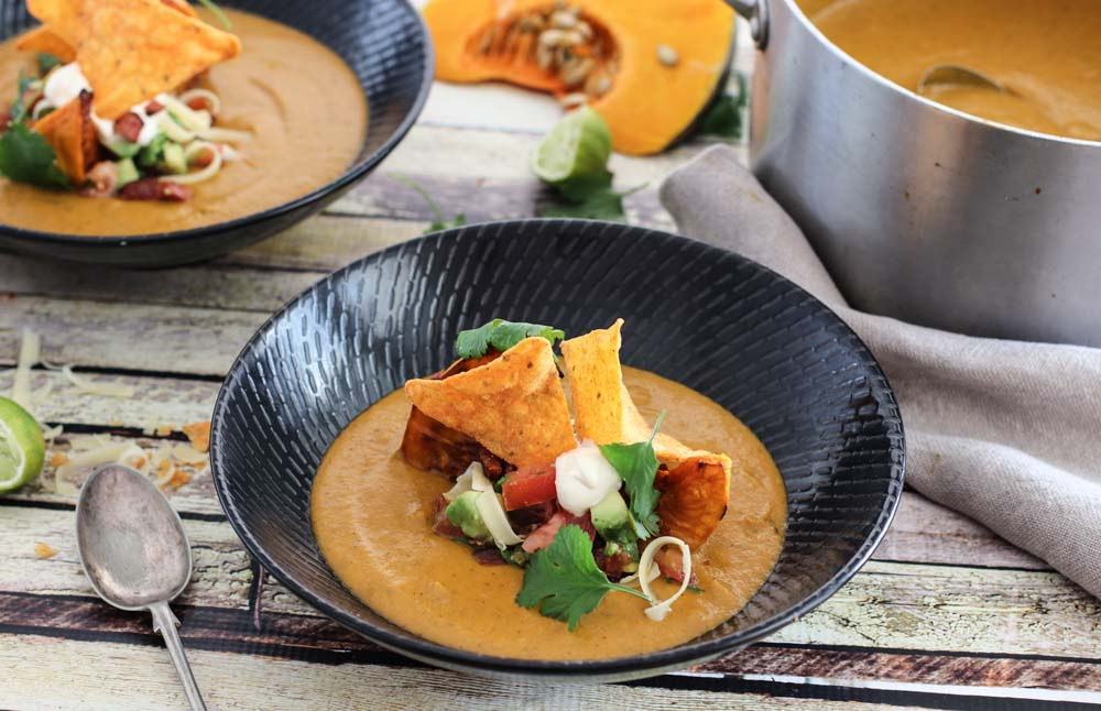 Pumpkin soup loaded with chorizo, cheese and avocado