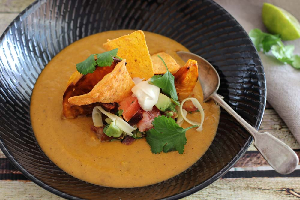 Pumpkin soup loaded up with chorizo, chips and sour cream