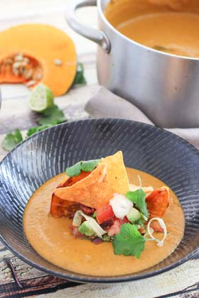 Pumpkin soup in a black bolw with salsa and chips