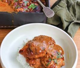 Butter Chicken in a bowl with baked chicken in the background