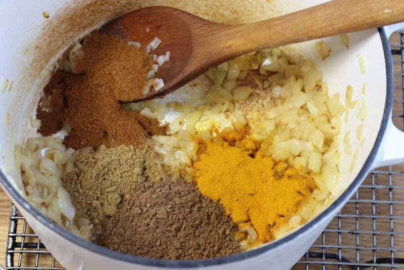 Spices for Butter chicken added to the pot with simmering onions
