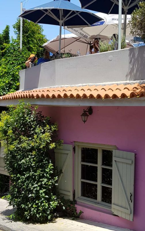A restaurant painted pink on a hill in Plaka, Athens