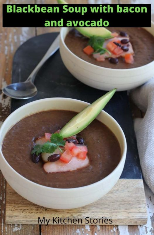 Blackbean soup in a white bowl with salsa and bacon