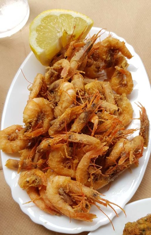 Deep fried school prawns on a white plate in Athens