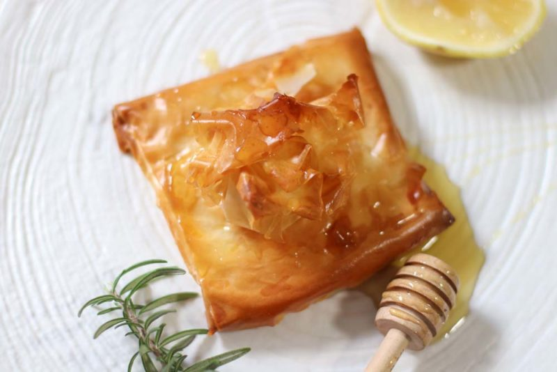 Feta baked in filo pastry with honey on a white plate