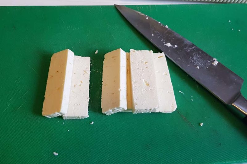 Cut feta on a green board ready to be used