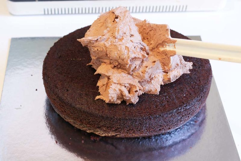 Chocolate cake with buttercream icing being spread on top