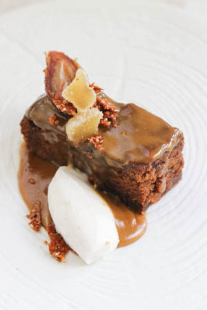 date and Ginger pudding on a white plate with coconut cream