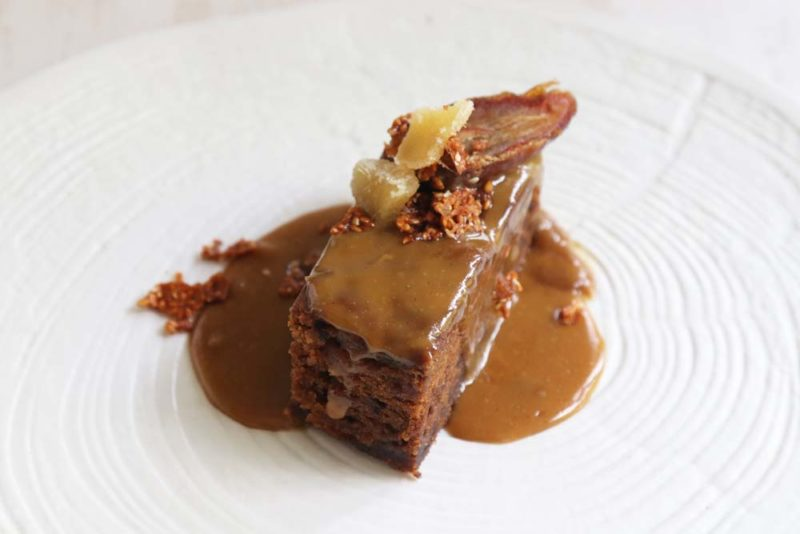 A date and ginger pudding on a white plate with sauce