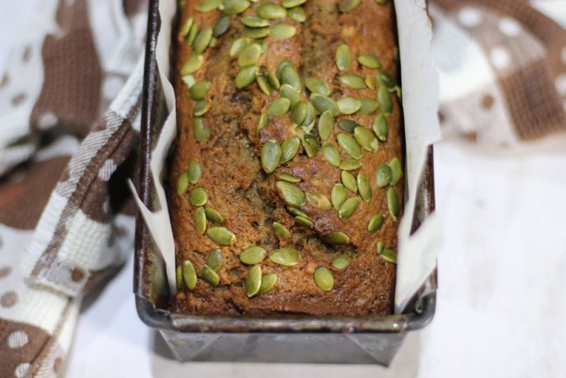 A loaf odf banana bread with pepita seeds on top