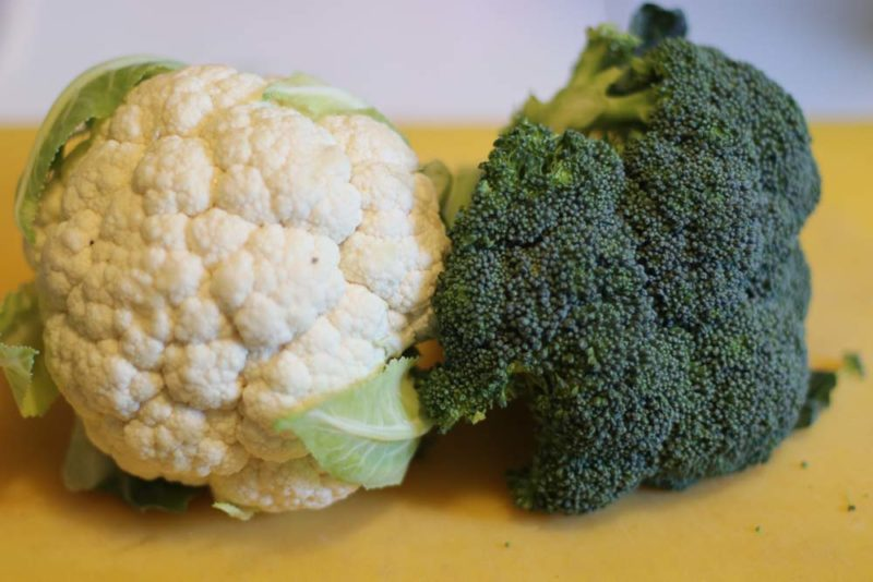 broccoli and cauliflower whole heads on a bench