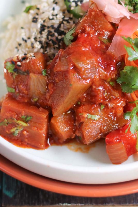 A closeup of braised eggplant with ginger and tomato