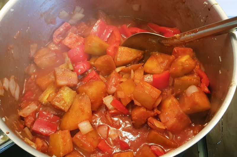 Adding all the ingrediants to sweet and sour eggplant in a pot