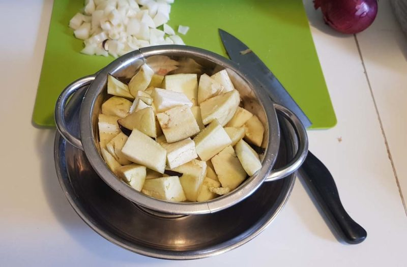 Salting and draining eggplant in a colander