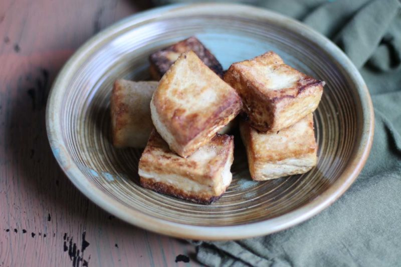 Fried tofu on a brown plate