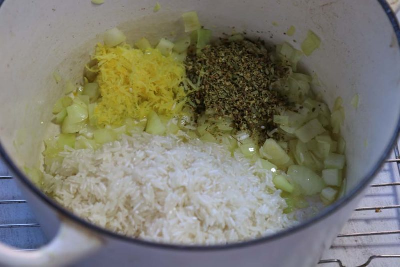 Onions, garlic and spices in a pot with rice