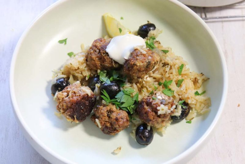 Feta and lamb balls with lemon rice on a blue plate