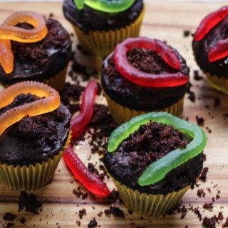 Cupcakes on a board with cake crumbs and worms for Halloween