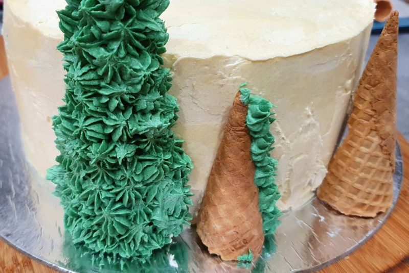 A cake with three christmas trees and buttercream