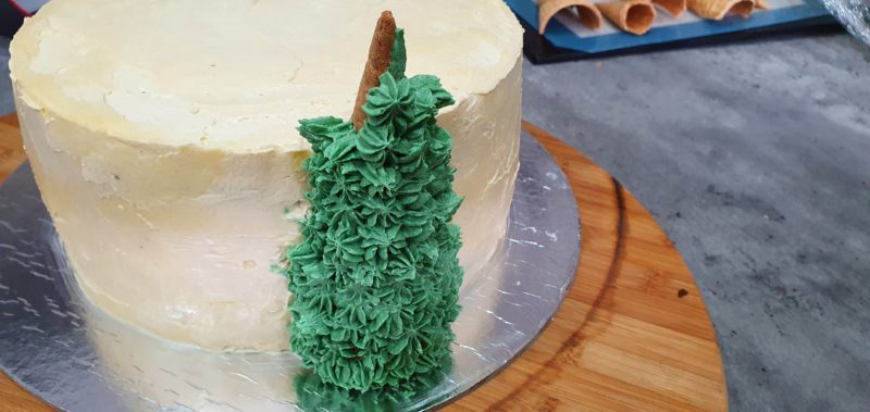 Finishing a christmas cake with trees