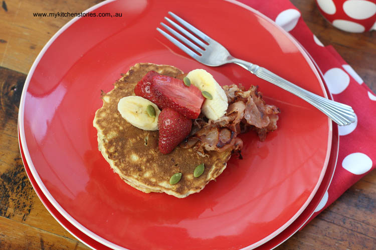 gluten free pancakes on a red plate with bananas