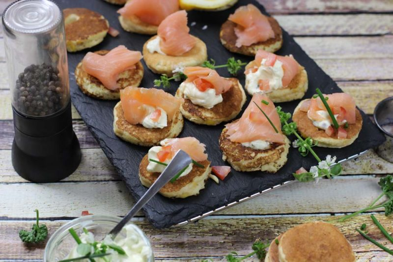 corn piklets on a black tray with smoked salmon and cream