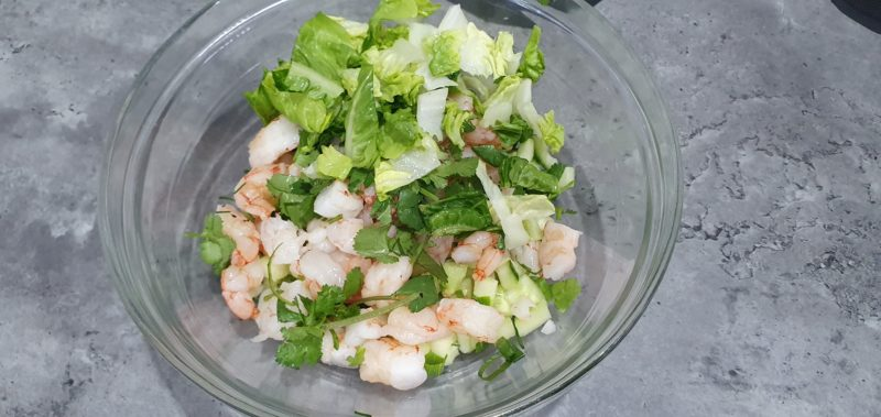 A bowl with salad of prawns, water chestnuts and shallots
