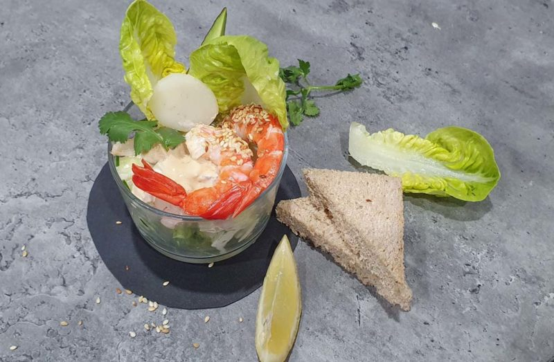 A prawn cocktail in a glASS WITH BROWN BREAD AVOCADO AND CREAMY DRESSING