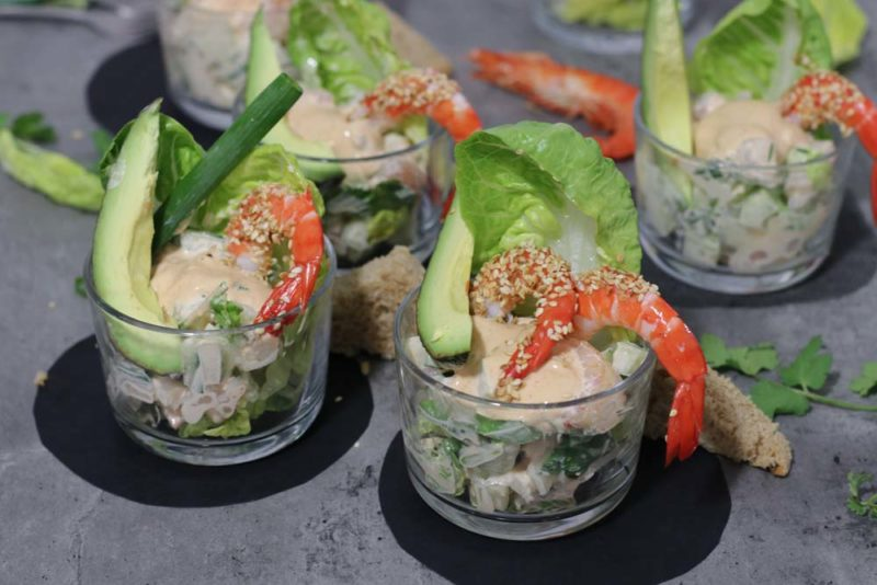 A group of glasses full of prawn salad with prawns hanging off the sides