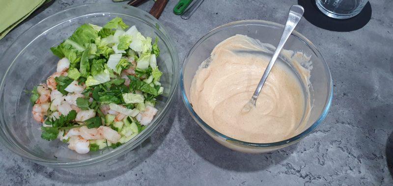 Prawns salad with a side of salad dressing