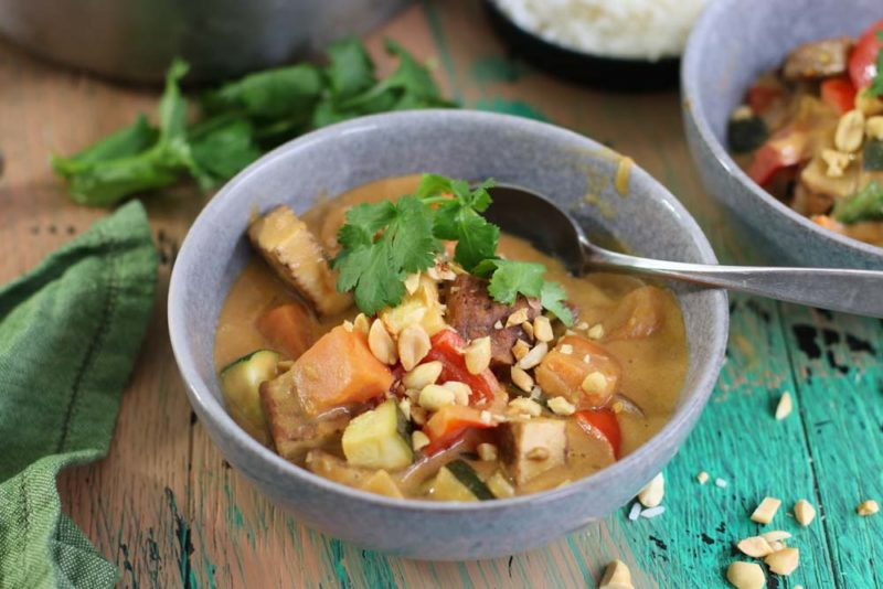 A colourful bowl of vegetables with peanut sauce