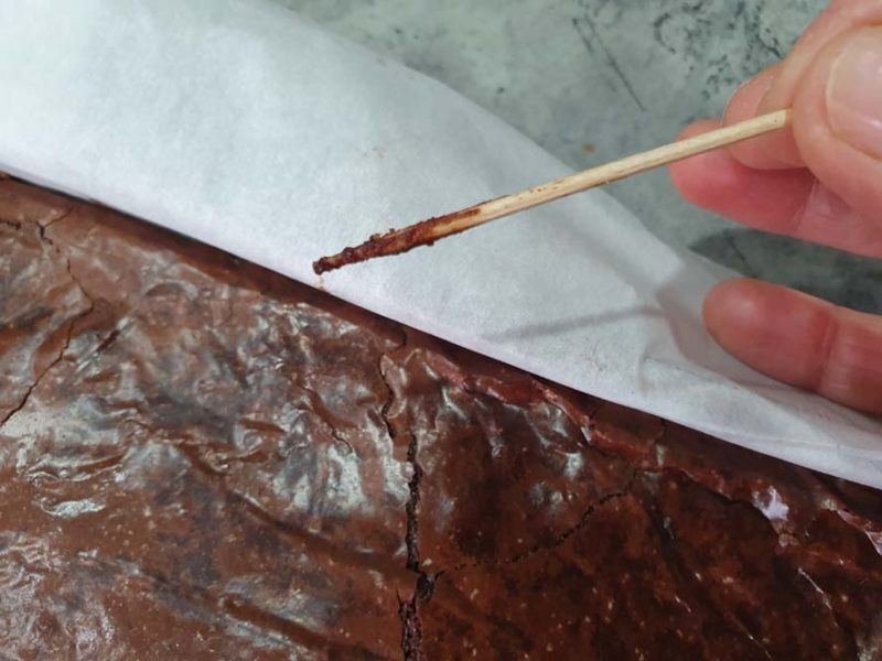 Testing cooked brownies with a toothpick